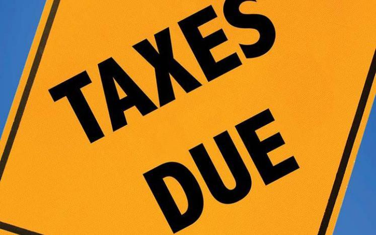 Yellow warning sign that says taxes due